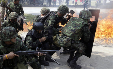 """Soldiers run past a fire during a fight with anti-government """"red shirt"""" protesters at Thaicom Teleport and DTH Centre on the outskirts of Bangkok in Pathum Thani province"""