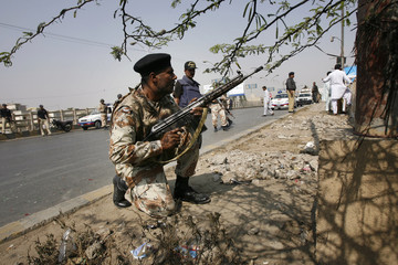 Pakistani paramilitary forces keep guard after arriving to the site of a target killing in Karachi
