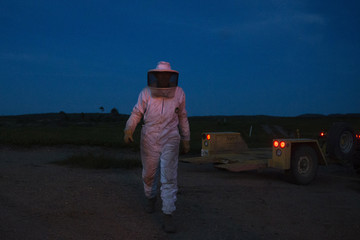 Beekeeper Harvey is illuminated by lights from machinery as he transfers Italian honey bee colonies to fields of crops for pollination, near Columbia Falls, Maine