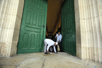 Palestinian men sweep near the entrance to al-Aqsa mosque following clashes between Palestinians and Israeli police in Jerusalem's Old City