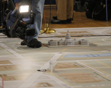 A news videographer films a model of the U.S. Capitol on a large map at the DC Armory in Washington