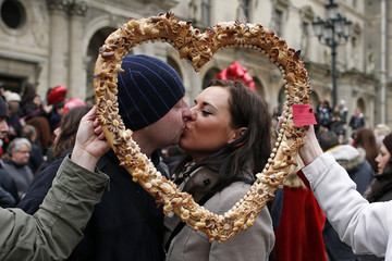 A couple share a kiss during a kissing flashmob event to celebrate Valentine's Day in front of the Pyramid at the Louvre Museum in Paris