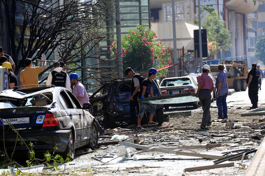 Workers clean the area from broken glass as forensic inspectors examine the site of an explosion that occurred on Sunday outside the headquarters of the Lebanese Blom Bank in Beirut