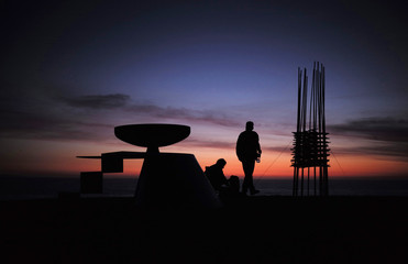 """Visitors to the """"Sculpture by the Sea"""" exhibition are pictured among various works before sunrise at Sydney's Bondi Beach"""