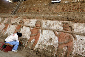 A worker restores images of a procession of prisoners, at a wall in the temple of Huaca de La Luna in Trujillo