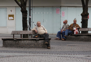 People sit on benches in front of an empty shop in the western city of Bottrop