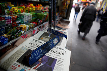 The cover of the Wall Street Journal newspaper is seen with other papers at a news stand in New York