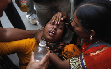 People assist the relative of a patient who died in the 2011 AMRI Hospital fire during a commemoration in front of the hospital in Kolkata