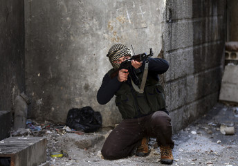 A Free Syrian Army fighter aims his rifle in Mleha suburb of Damascus