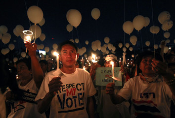 Pro-government supporters hold candles and white balloons during an election campaign in Nonthaburi province