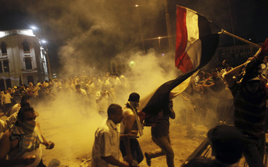 Supporters of deposed Egyptian President Mohamed Mursi run from tear gas fired by riot police during clashes at Ramses Square in Cairo