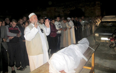 Free Syrian Army fighers and residents pray near the body of Mahammad Zakour during his funeral near Idlib