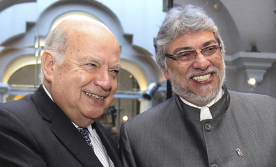 OAS Secretary General Insulza and ousted Paraguayan President Lugo smile before a private meeting in Asuncion