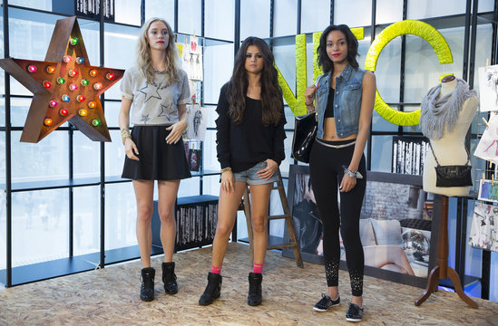 U.S. actress and singer Gomez poses with two models wearing pieces of collection she has created for Adidas Neo label during its presentation in Berlin