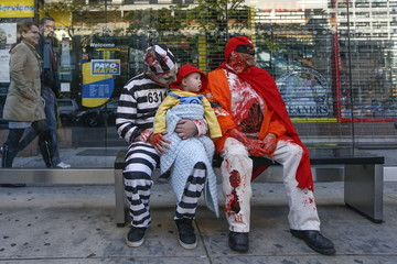Jason Bregartner and his son Jason Jr., 2, sit in costume with J.D. Mirable at a bustop during the NYC Zombie Crawl in New York