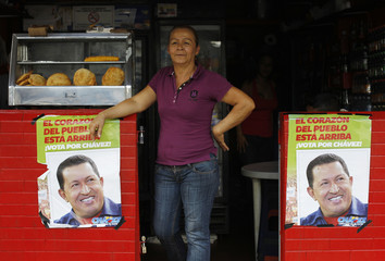 A woman stand in a restaurant between  pictures of Venezuela's President Hugo Chavez  in front of a military hospital, where Chavez is being treated, in Caracas