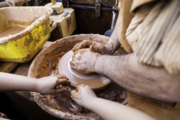 Person working clay with hands, traditional craft, potter