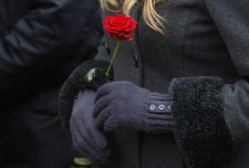 A woman holds a red rose as the coffin of Austrian entertainer Peter Alexander lies in state at the Zentralfriedhof in Vienna