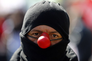 A man wearing a clown's nose attends a demonstration in downtown Santiago