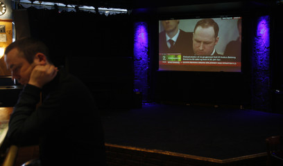 Man reads a newspaper as the live broadcast of the trial of Norwegian mass killer Anders Behring Breivik runs on a screen in the background at a bar in Oslo