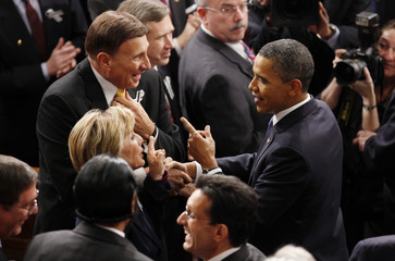 U.S. President Barack Obama speaks with Reps. Boxer and Mica before his annual State of the Union Address in Washington