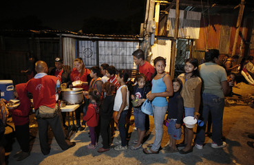 People line up to receive food in Triangulo de la Solidaridad, a low-income neighbourhood, north of San Jose