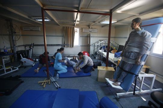Injured Syrian men receive physical therapy at a small clinic near the Turkish-Syrian border in the southeastern city of Kilis