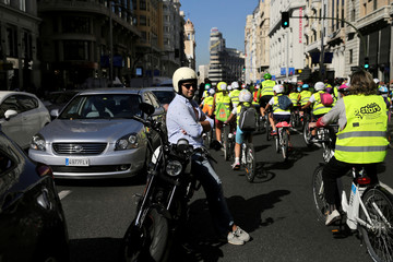 A man waits next to his motorbike as scholars on bicycles ride past as part of the framework of the European Mobility Week at Gran Via street in central Madrid, Spain