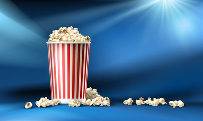 Vector illustration of a red and white cardboard bucket with popcorn in a realistic style isolated on a blue background with light rays