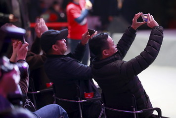 Alibaba founder and chairman Jack Ma (R) takes a picture of a screen showing real-time data of transactions at Alibaba Group's 11.11 Global shopping festival in Beijing