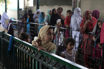 Girls line up to receive free food distributed at the Bari Imam Shrine in Islamabad