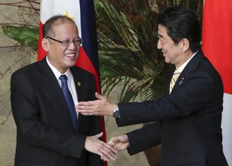 Japanese Prime Minister Shinzo Abe gestures next to Philippine President Benigno Aquino in Tokyo