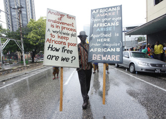 A man carries two placards during Emancipation Day Celebrations on the streets in the capital city of Port of Spain