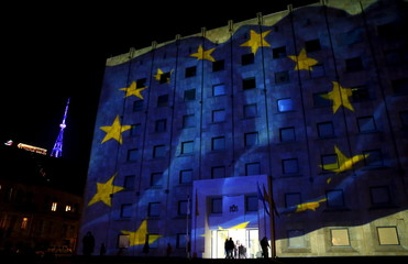 European flag is projected on the government building as TV tower is illuminated in blue in background in Tbilisi