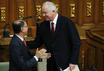Venezuelan Energy and Oil Minister Rafael Ramirez greets Electricity Minister Ali Rodriguez as they present their annual reports for 2010 in Caracas