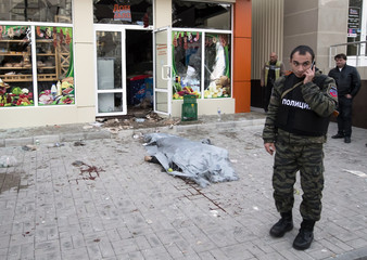 A policeman speaks on a phone next to the body of victim who was killed by recent shelling in front of a shop in Donetsk