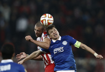Olympiakos' Kasami jumps for the header with Dnipro's  Konoplyanka during their Europa League round of 32 second leg soccer match at Karaiskaki stadium in Piraeus, near Athens