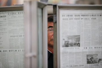 A man looks from behind newspapers displayed inside a subway station visited by foreign reporters on a government organised tour in central Pyongyang
