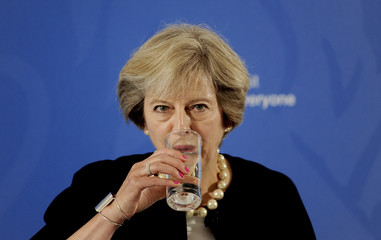 Prime Minister Theresa May takes a drink as she delivers a speech at the British Academy in London