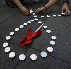 Activists distribute red ribbons and light up candles as they commemorate victims of the Human Immunodeficiency Virus, or HIV, during a flashmob in St.Petersburg