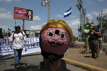 A boy dances while wearing a costume during a protest demanding fairer elections next year, in Managua