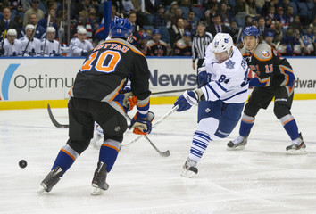 Toronto Maple Leafs Mikhail Grabovski shoots past New York Islanders Mike Mottau in their NHL hockey game in Uniondale