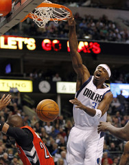 Mavericks' Terry dunks the ball on Raptors' Barbosa during the first half of their NBA basketball game in Dallas