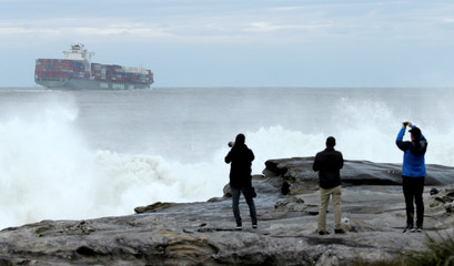 A China Shipping Line container ship sails out from Sydney's Botany Bay port as photographers take pictures of a surfing contest in heavy seas near Australia's largest city