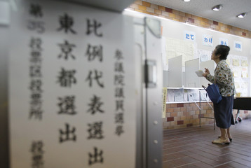 A woman looks at names of election candidates for the upper house election as she casts her ballot at a polling station in Tokyo