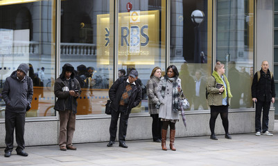 People stand outside a Royal Bank of Scotland building in central London