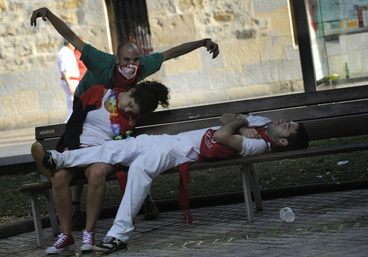 A reveller jokes around next to a sleeping couple during the San Fermin festival in Pamplona