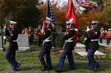 An honor guard unit marches carrying the flags of the United States and the U.S. Marine Corps before the Marine Band plays at the grave of former director John Philip Sousa, at the Congressional Cemetery in Washington