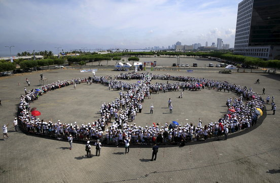 """Participants hold hands as they form a large peace sign during a """"Handshake for Peace"""" event at a parking lot of a mall in Pasay City"""