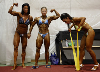 Hegedus, Szebeni and Mudra pose for a photo while warming up during a bodybuilding competition
